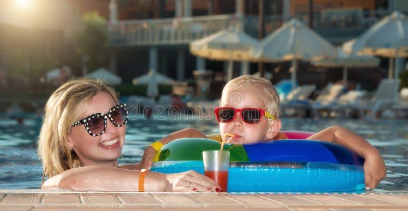 在水池的母亲和儿子饮用的鸡尾酒 热的暑假 库存照片