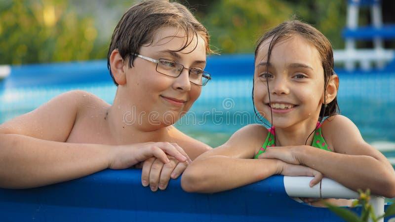 在水池的活动 逗人喜爱的孩子-姐妹和兄弟游泳和使用在游泳池的水中在aquapark 库存图片