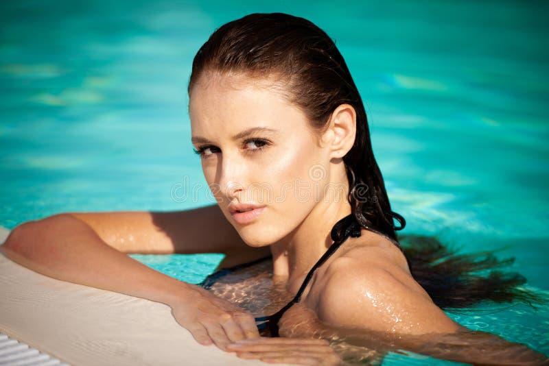 在水池的美好的年轻女人游泳在一个热的夏日 免版税图库摄影