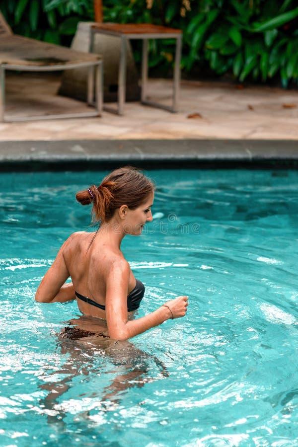 在水池的苗条被晒黑的妇女游泳 休息和温泉 ?? 库存照片