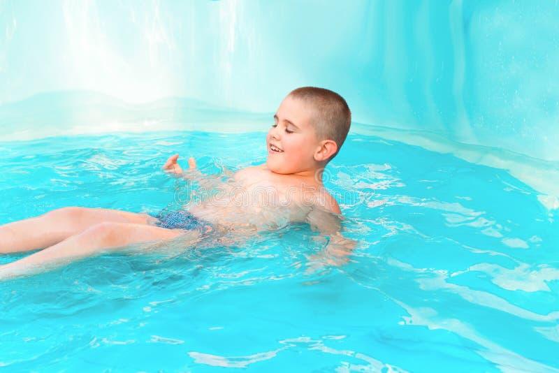 在水池的逗人喜爱的男孩游泳用绿松石水在夏天休假 免版税库存照片
