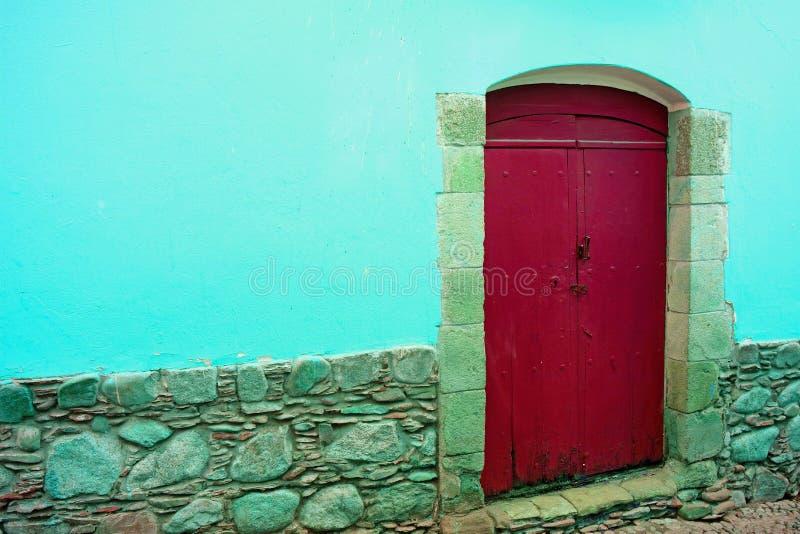 在水泥和石墙上的红色木门在水色蓝色 免版税库存图片