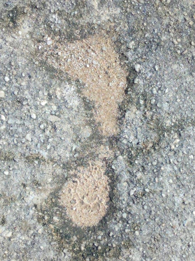 在水泥地面的脚印刷品 免版税库存图片
