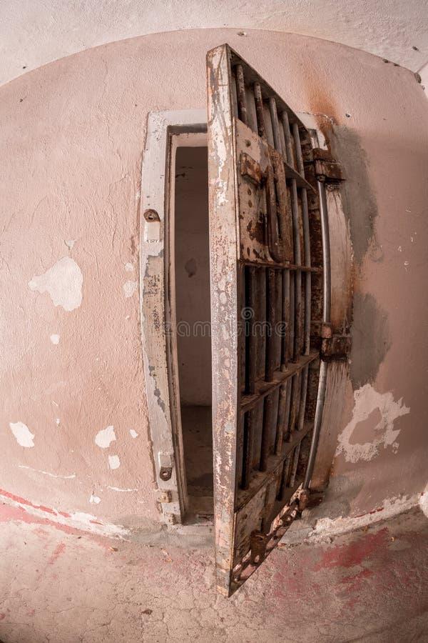 在水泥墙壁上的钢牢房门 免版税库存图片