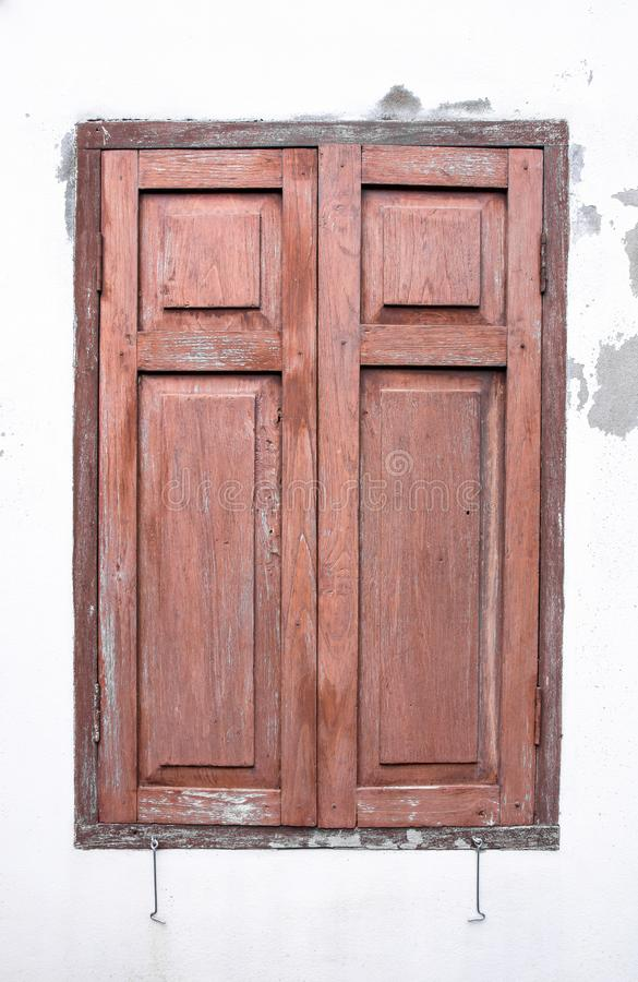 在水泥白色墙壁上的老木窗口 库存照片