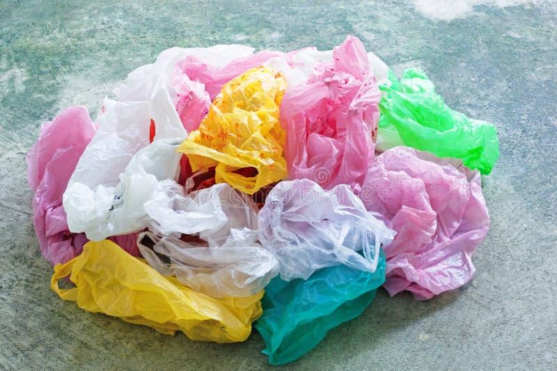 在水泥背景的五颜六色的塑料袋 库存照片