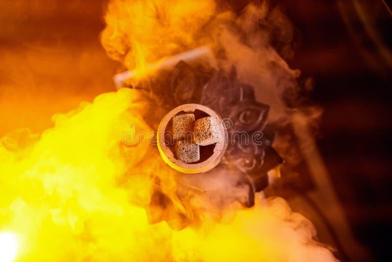 在水烟筒碗,顶视图的炙热的余烬,在颜色背景 库存照片