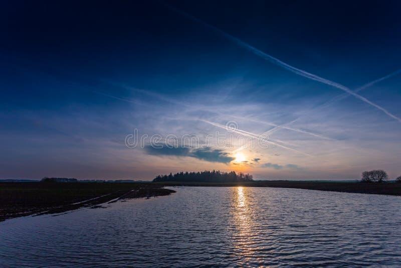 在水的冷的蓝色晚上日落 库存照片