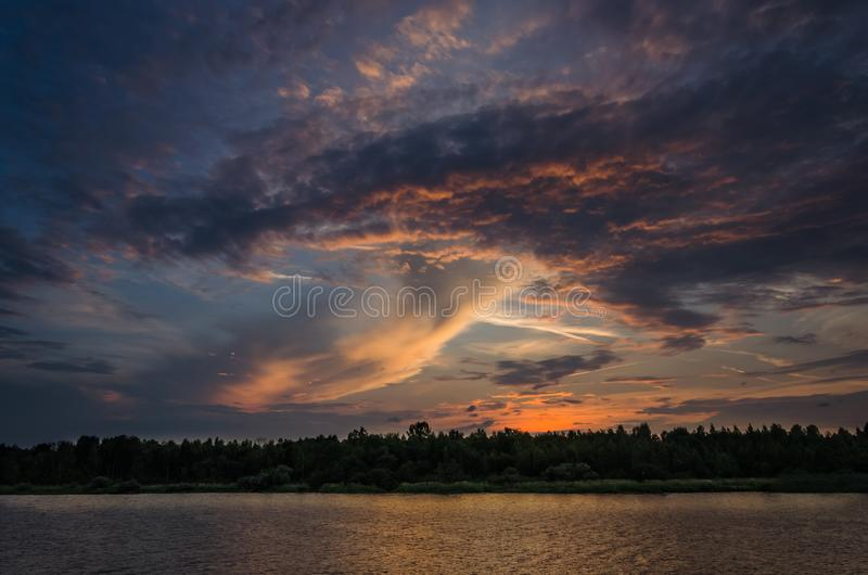 在水的剧烈的云彩在日落期间 免版税图库摄影