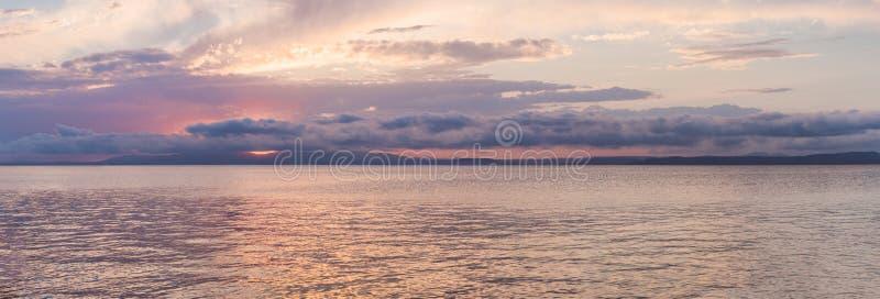 在水的发光的天堂日落 在海的紫色日落 库存图片