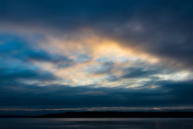 在水的多云蓝色金黄黄色天空日出日落 免版税库存照片
