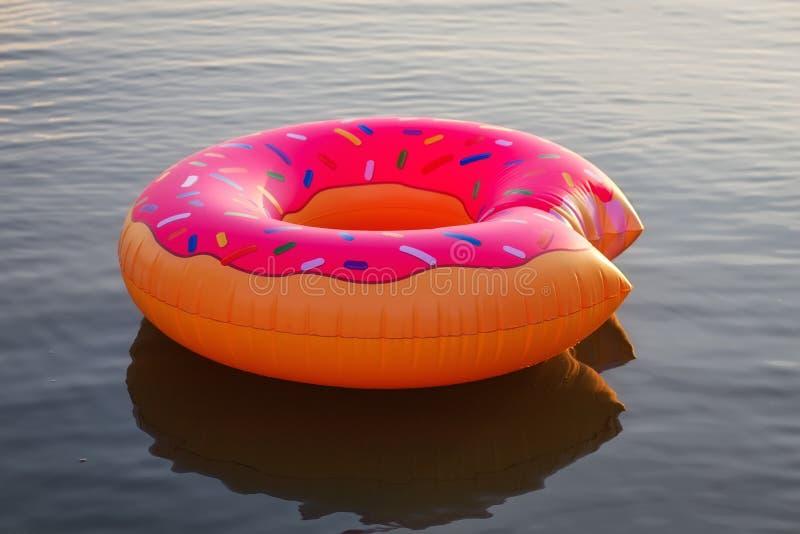 在水的大可膨胀的多福饼在日出时间 行家被洒的多福饼浮游物在湖 库存图片
