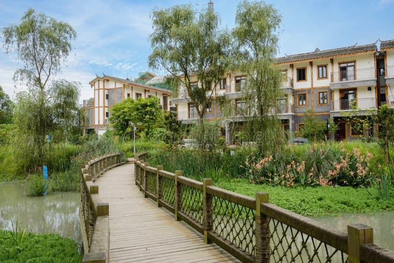 在水的木人行桥对湖边在s的住宅大厦 免版税库存照片
