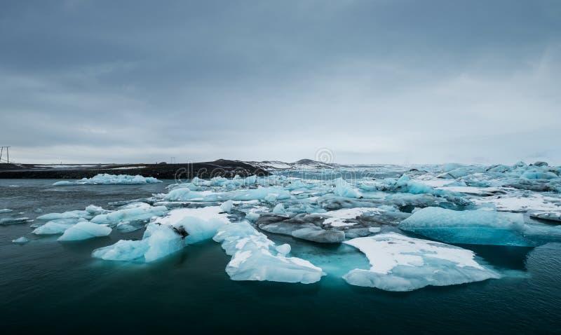 在水的熔化的冰在Jokulsarlon湖在南冰岛在多云天 全球性变暖 免版税库存图片