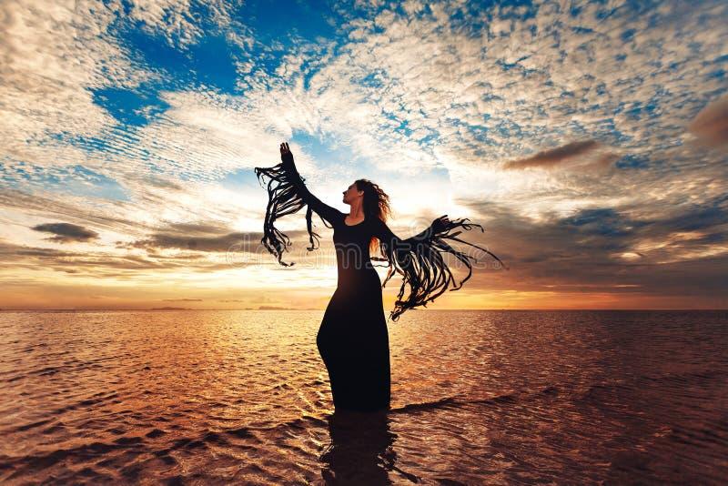 在水的端庄的妇女跳舞 日落和剪影 库存照片