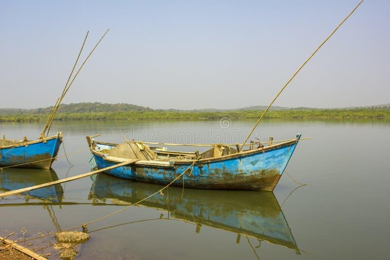 在水的老破旧的蓝色小船反对河的背景 图库摄影