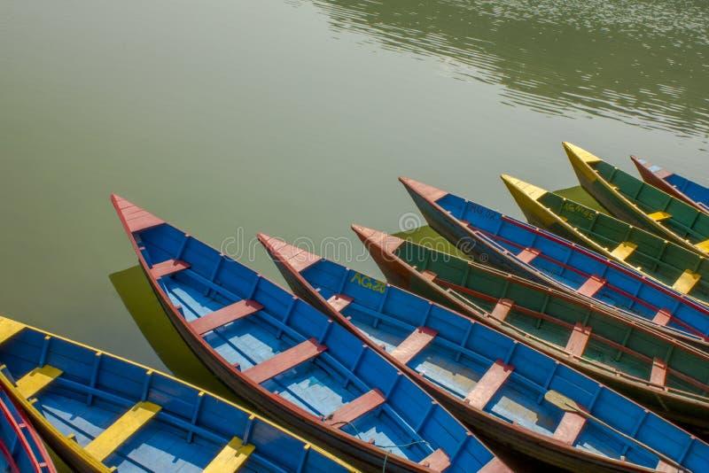 在水的蓝色红色黄绿色老木小船 在湖的划艇 库存照片