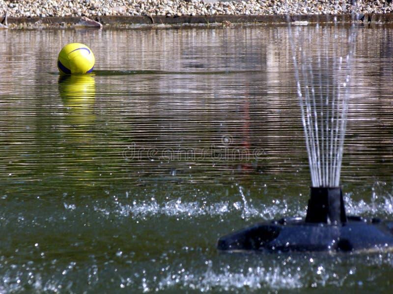 在水的黄色球与喷泉装喷水器 库存图片
