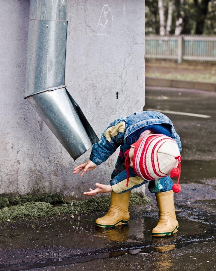 在水管之下的孩子洗涤的现有量。 免版税库存照片
