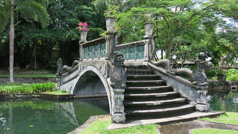 在水运河的装饰石桥梁在皇家庭院里 与巴厘语文化的元素的历史建筑 免版税库存图片