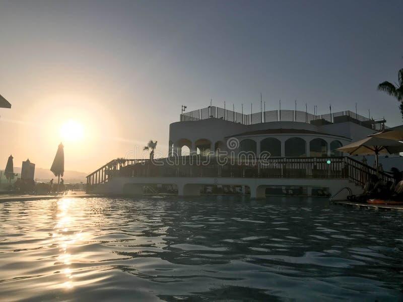 在水附近的一个大石大厦,反对蓝天的一个水池和大太阳,日落在热带海边的晚上关于 免版税库存照片