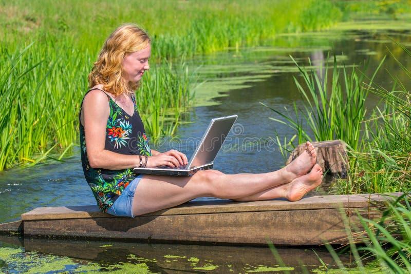 在水附近的少妇运行的膝上型计算机本质上 免版税库存照片