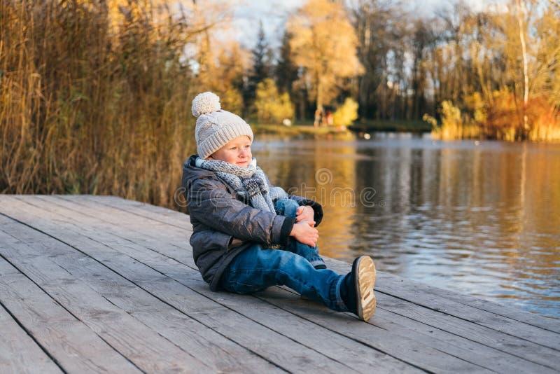 在水附近的逗人喜爱的时髦的男孩 免版税库存图片
