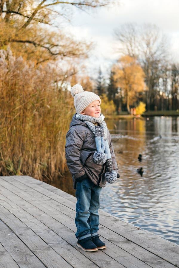 在水附近的逗人喜爱的时髦的男孩 免版税图库摄影