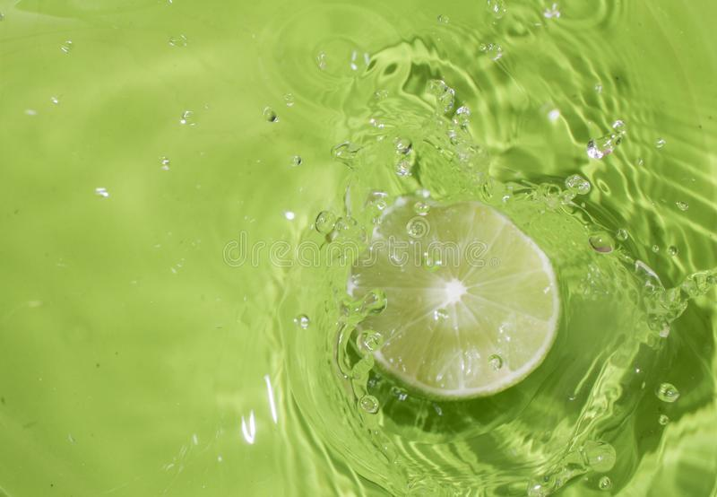 在水飞溅的绿色柠檬 免版税库存照片