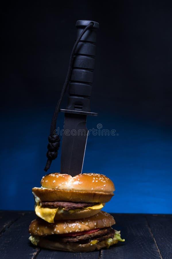 在汉堡埋置的一把大刀子 双重汉堡用肉 免版税库存照片