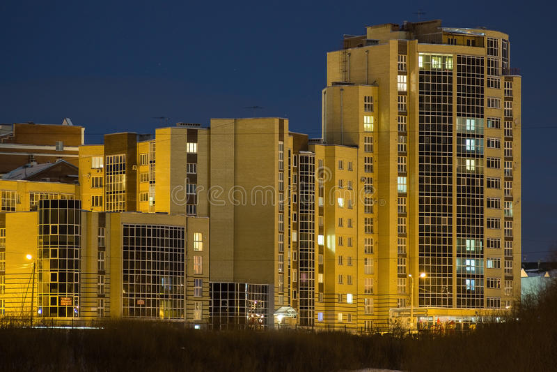 在江边的多层的大厦在晚上 库存图片