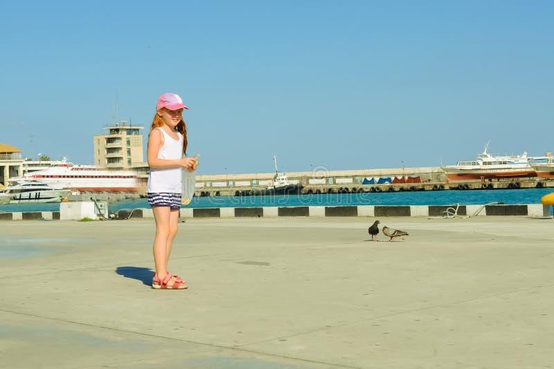 在江边的小女孩哺养的鸽子 免版税库存图片