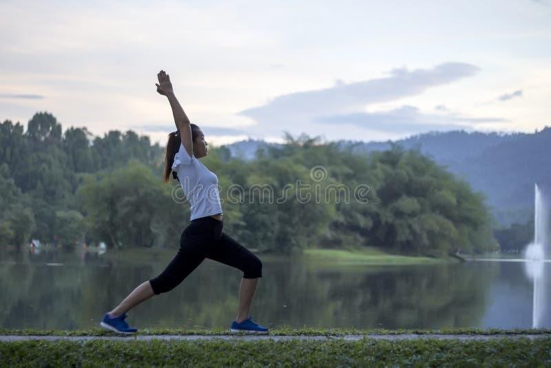 在池塘前面的平安的女子瑜伽锻炼 免版税库存照片