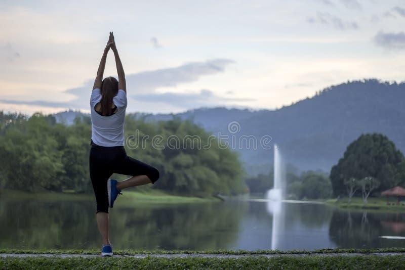 在池塘前面的平安的女子瑜伽锻炼 免版税图库摄影