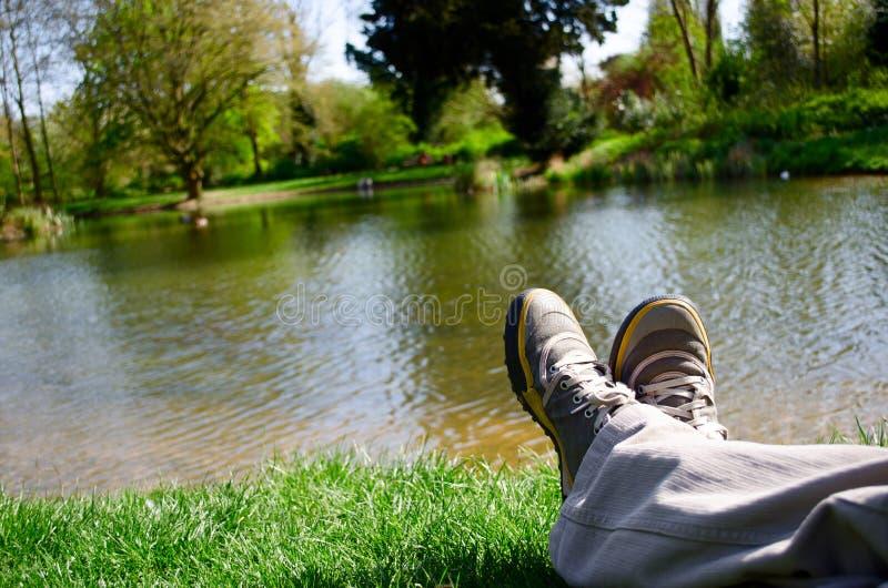 在池塘旁边的腿 库存图片