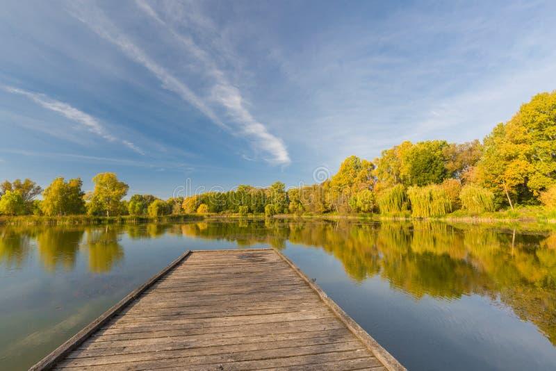 在池塘的反射日落的在秋天,木码头,镇静天气 季节性风景 库存图片