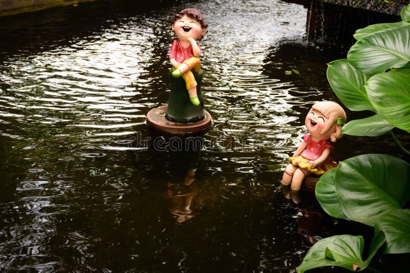 在池塘结合玩偶由黏土制成在小庭院 库存照片