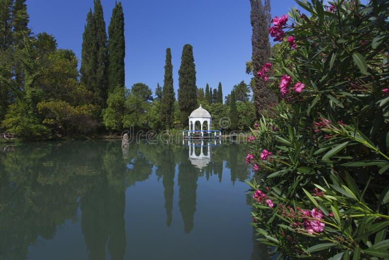在池塘附近的白色亭子在美丽的公园 免版税库存图片
