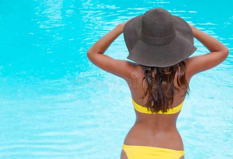 在池妇女附近的比基尼泳装帽子 免版税图库摄影