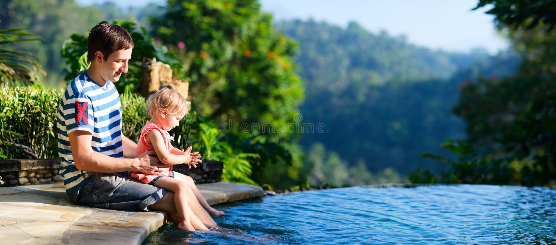 在池游泳附近的女儿父亲 免版税库存照片