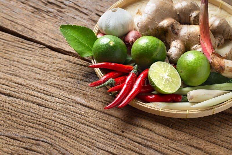 在汤姆辣汤木头背景草本成份的传统泰国食物烹调  免版税库存图片