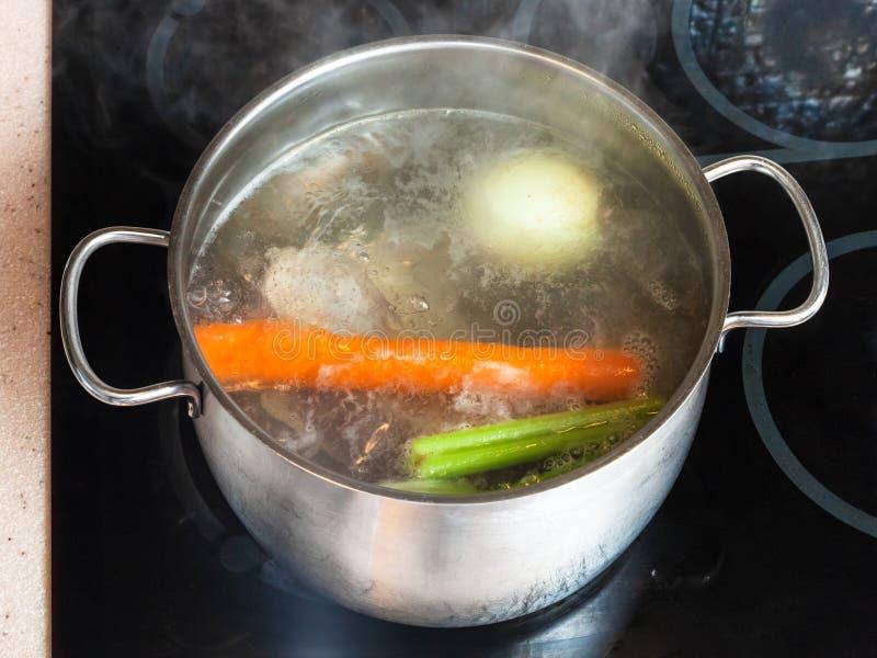 在汤锅的煮沸的肉存量在陶瓷烹饪器材 免版税图库摄影