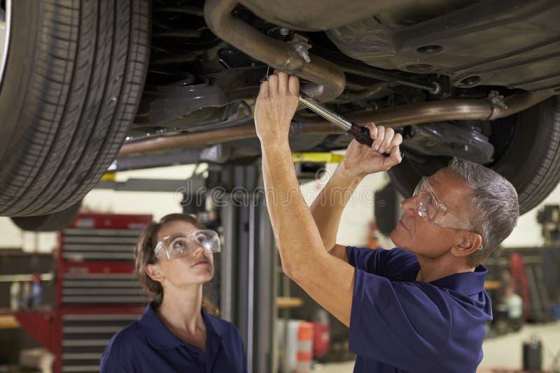 在汽车下的男性和女性技工 免版税库存照片