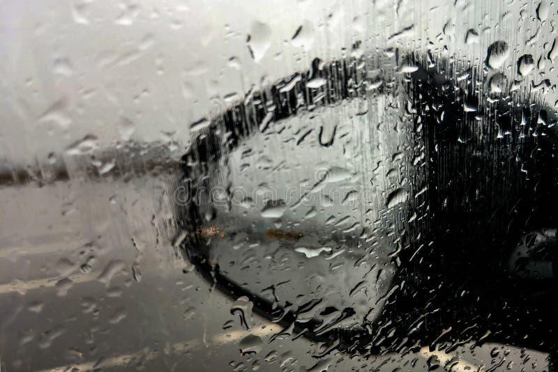 在汽车之外的雨珠在下雨在汽车停车处的天中 从驾驶席的好看法 库存图片