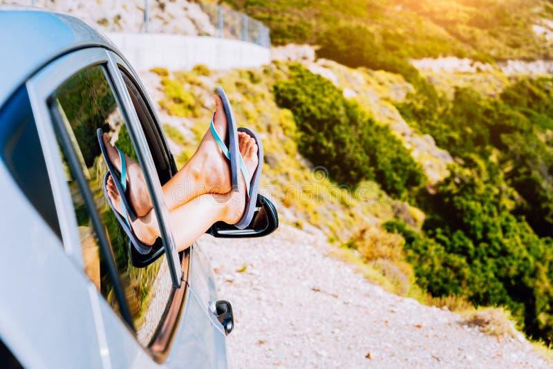 在汽车云彩概念概念性复制自由节假日图象行程道路空间夏天旅行之上绊倒假期视窗妇女 妇女腿在汽车的窗口在希腊海岛弯曲道路  免版税库存图片