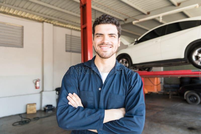 在汽车修理店横渡的微笑的工作者常设胳膊 库存照片
