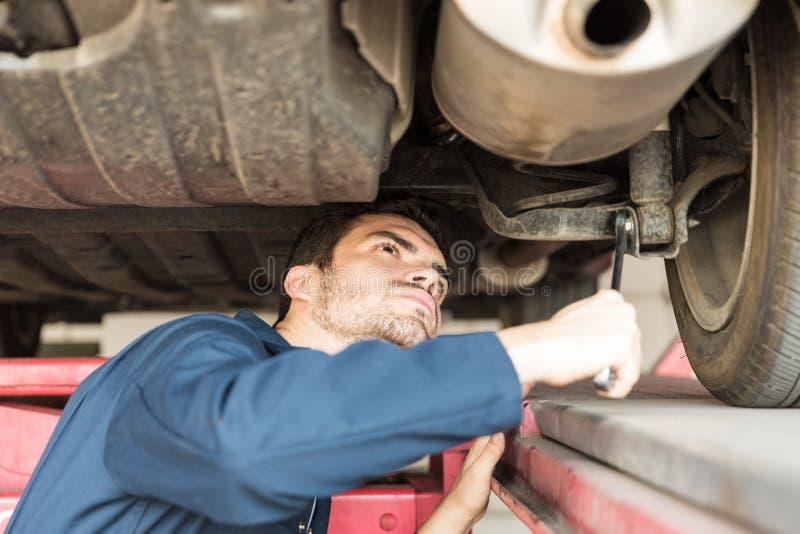 在汽车修理店的汽车专家的审查的汽车 库存图片
