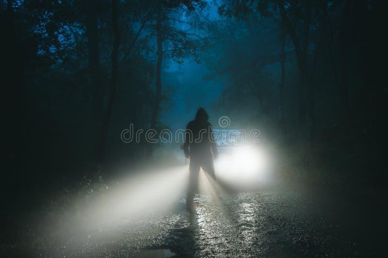在汽车前面的一个阴险戴头巾图身分 在一条鬼的森林公路上在一个有雾的晚上 库存照片