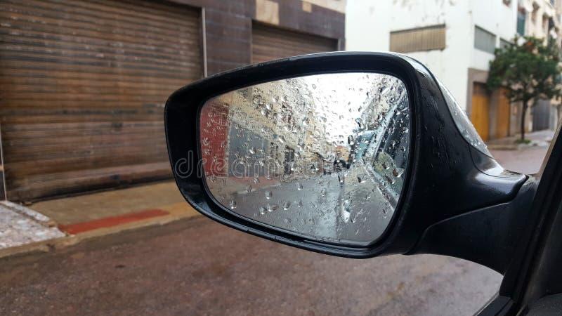 在汽车后视镜的雨珠 免版税库存图片