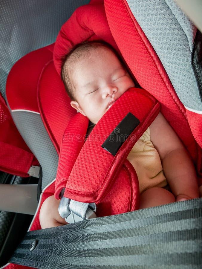 在汽车座位的新出生的婴孩睡眠 免版税库存照片
